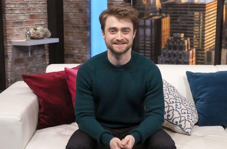 Daniel Radcliffe sitting on a sofa.