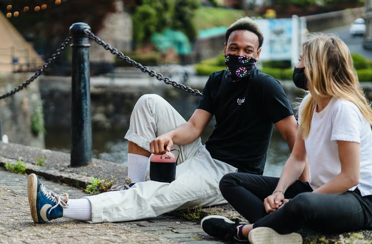 A guy and a girl sitting down on the ground wearing face masks.
