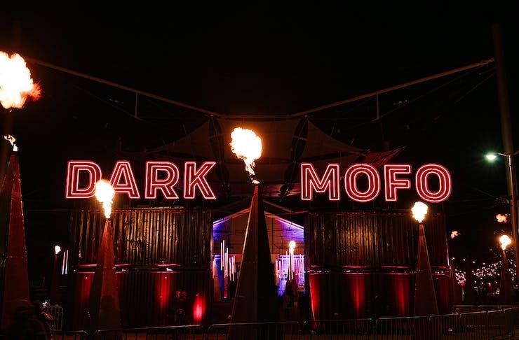 A red neon Dark Mofo lights up the night sky.