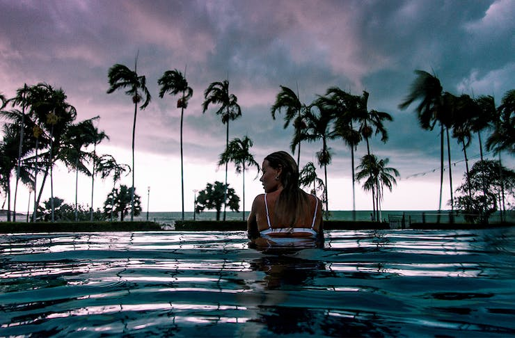 a woman in a pool at one of Darwin's best hotels, fringed with palm trees, at dusk.