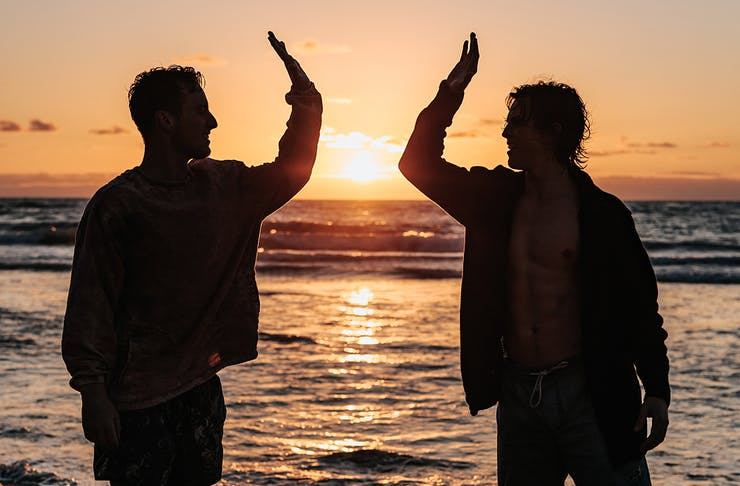 two men high five on the beach at sunset