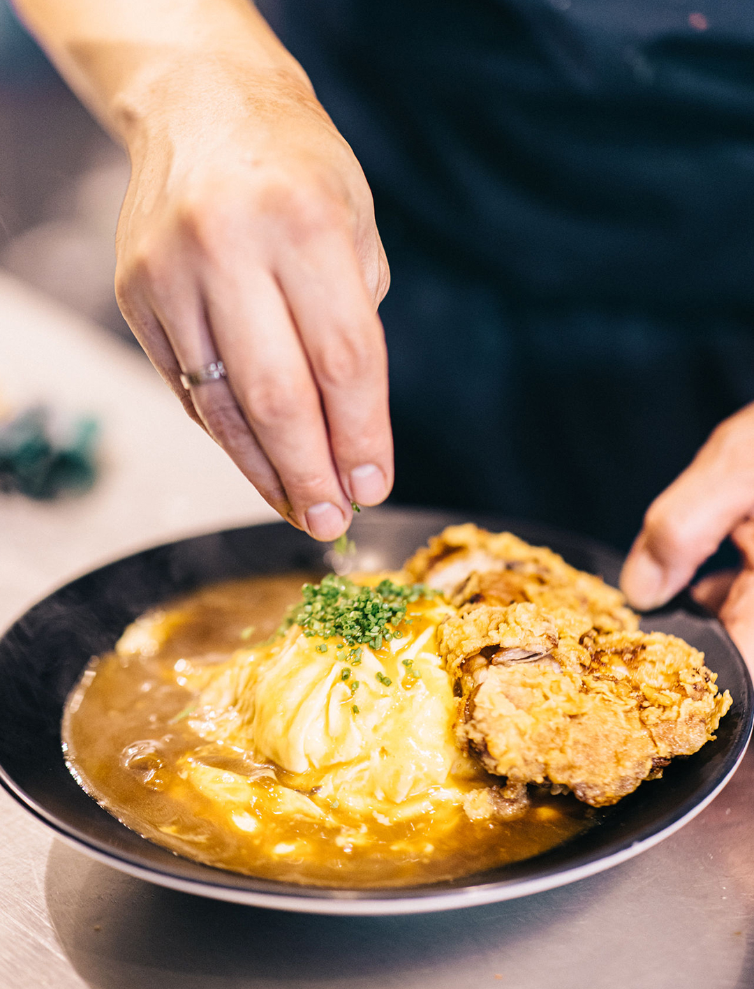 hands mixing omurice in bowl