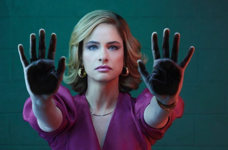 A woman holds up her hands, flat against a glass wall.