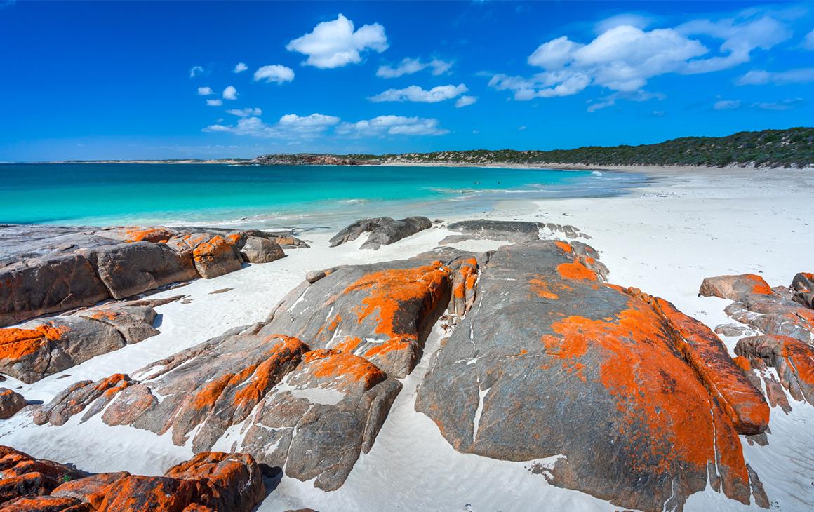 Orange tinged rocks line Dolphin Beach.