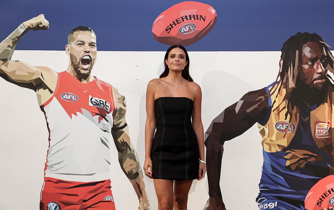 Dom Gauci poses in front of a wall featuring her AFL art work