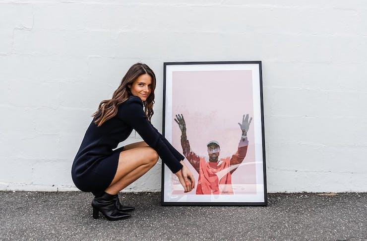 Artist Dom Gauci crouches down next to a framed piece of her art work