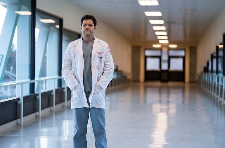 A doctor stands in the hallway of a hospital, his hands in the pocket of his jacket.
