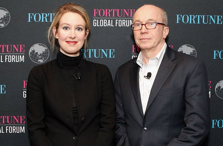Elizabeth Holmes poses in front of a media wall