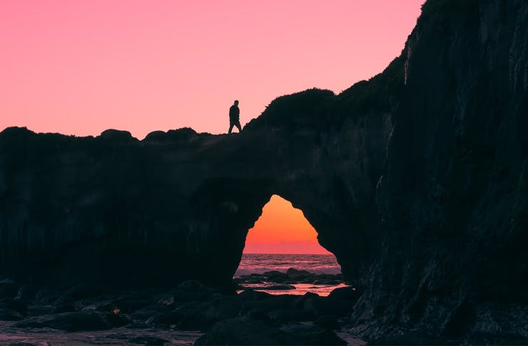 A person walking over a rock formation by the ocean at twilight.