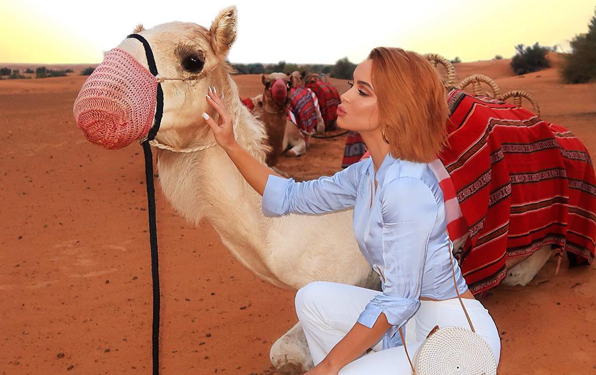 Ellie leans into give a camel a kiss in the UAE desert.
