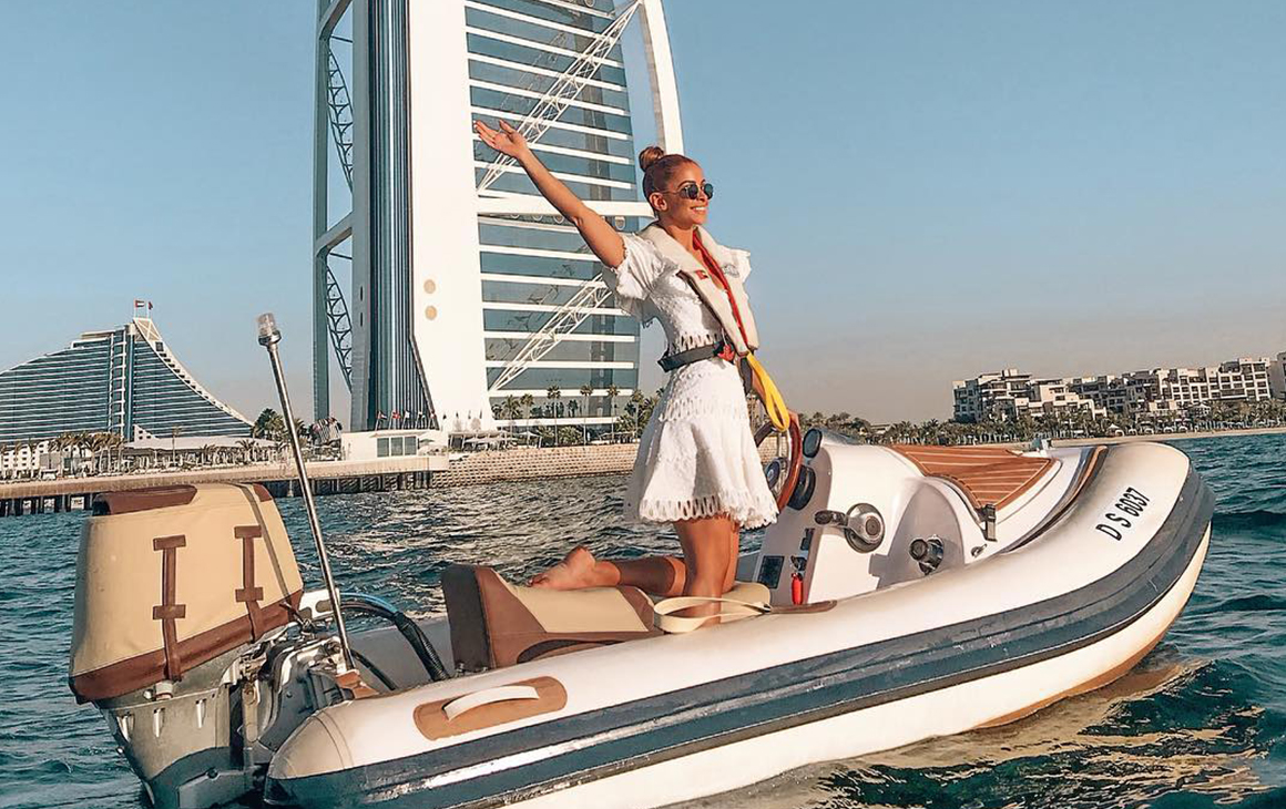 Ellie stands on a speed boat with her arms in the air on sea in Dubai. Behind her is tall buildings and the desert.