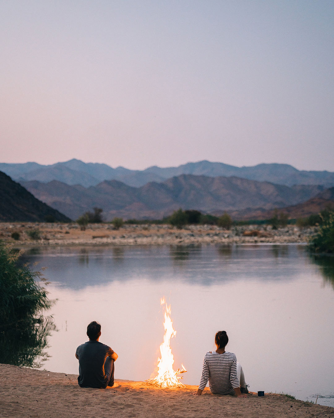 two people sitting on edge of river bank with small fire, looking out onto river at sunset