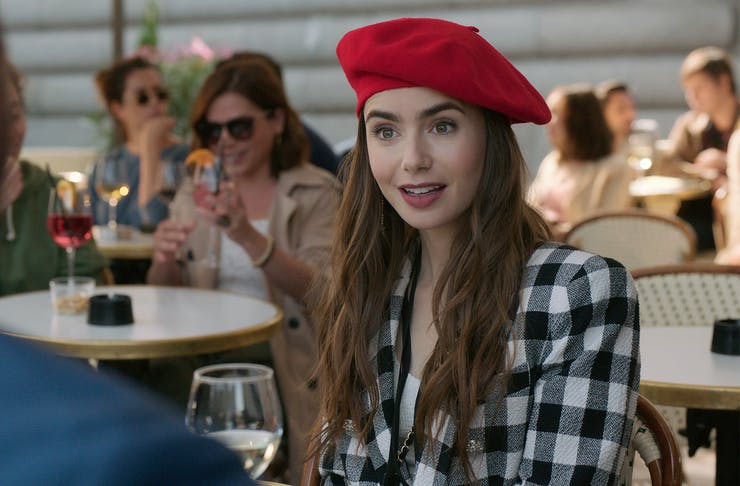 A young woman in a red beret looks shocked while mid conversation at lunch.