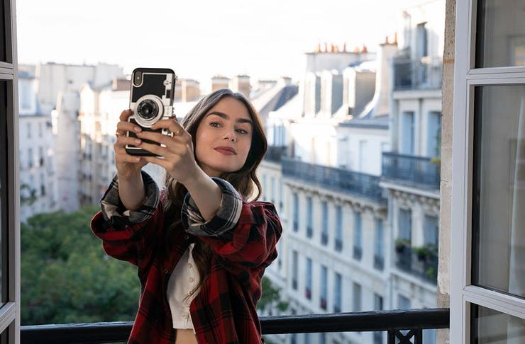A young woman takes a selfie from a window in Paris.