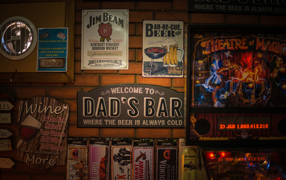 a pinball machine and selection of signs cover the wall of a pub.