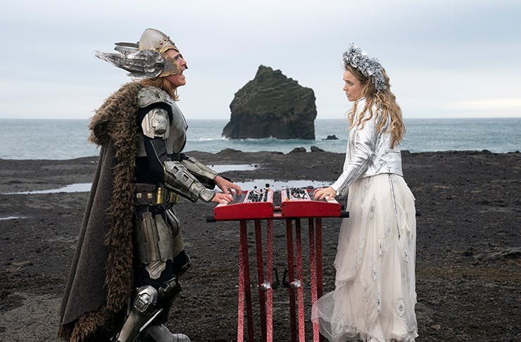 will ferrell and rachel mcadams dressed up as vikings playing piano on a volcanic ridge in Netflix's movie eurovision song contest the story of fire saga