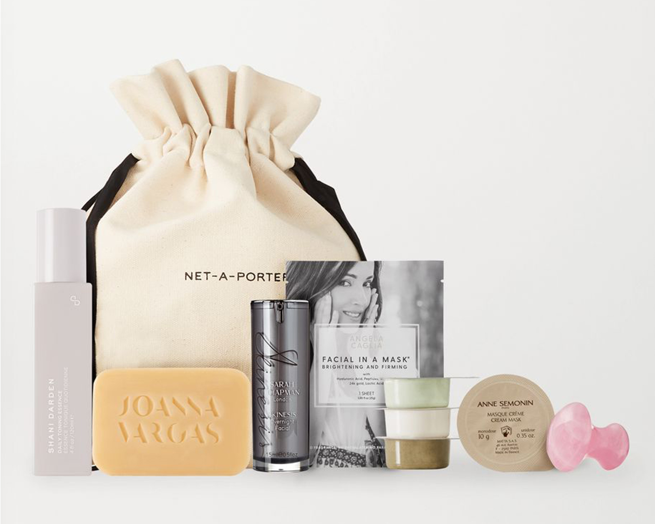 A bag sits on a table with a variety of beauty products in front of it.
