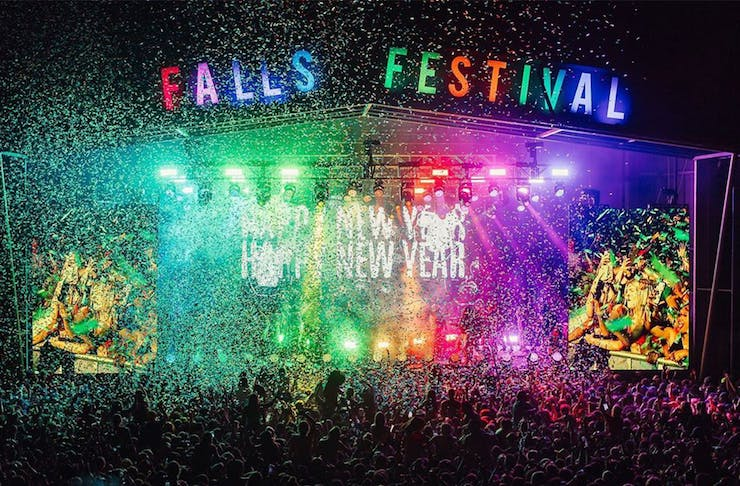A music stage at falls festival lit with a rainbow of coloured lights.