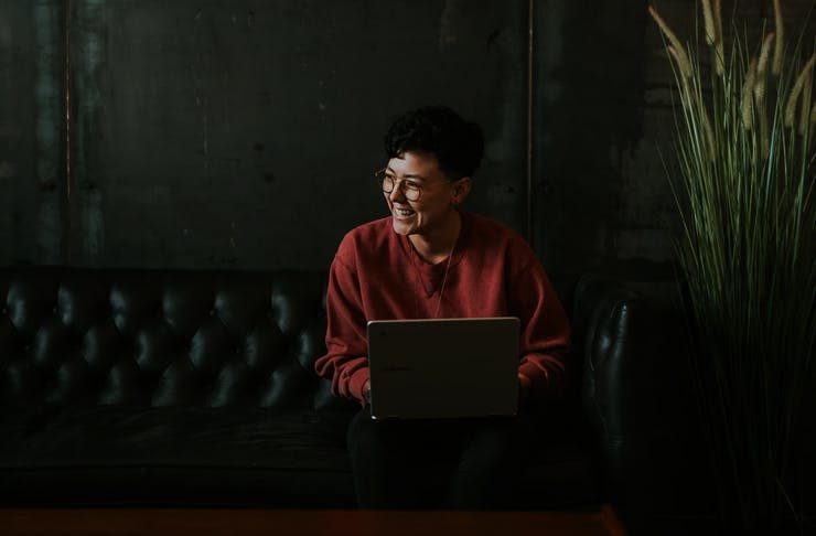 girl sitting on couch with laptop