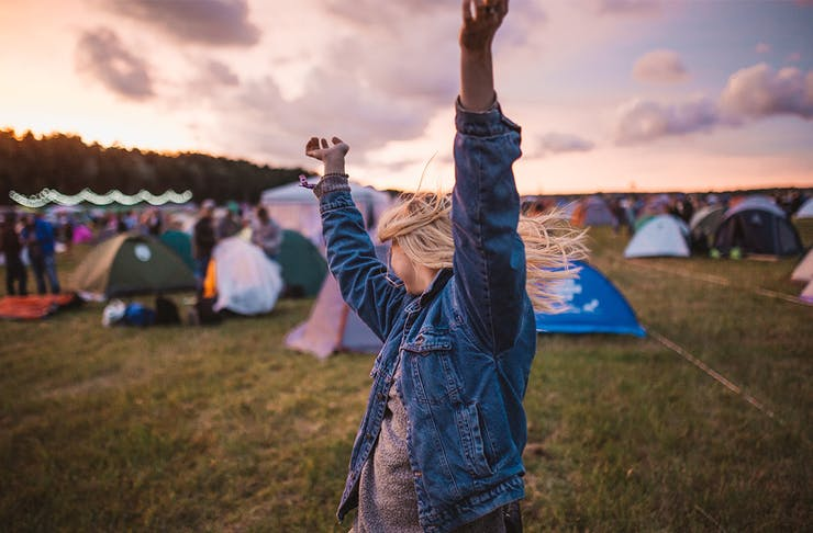 a young woman throws her arms up in the air. A cluster of tents are behind her.