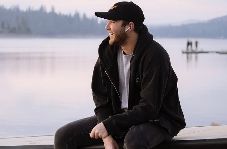 a man wearing airpods, smiles while sitting on the edge of a lake.