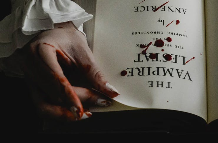 bloody hand turning page of book