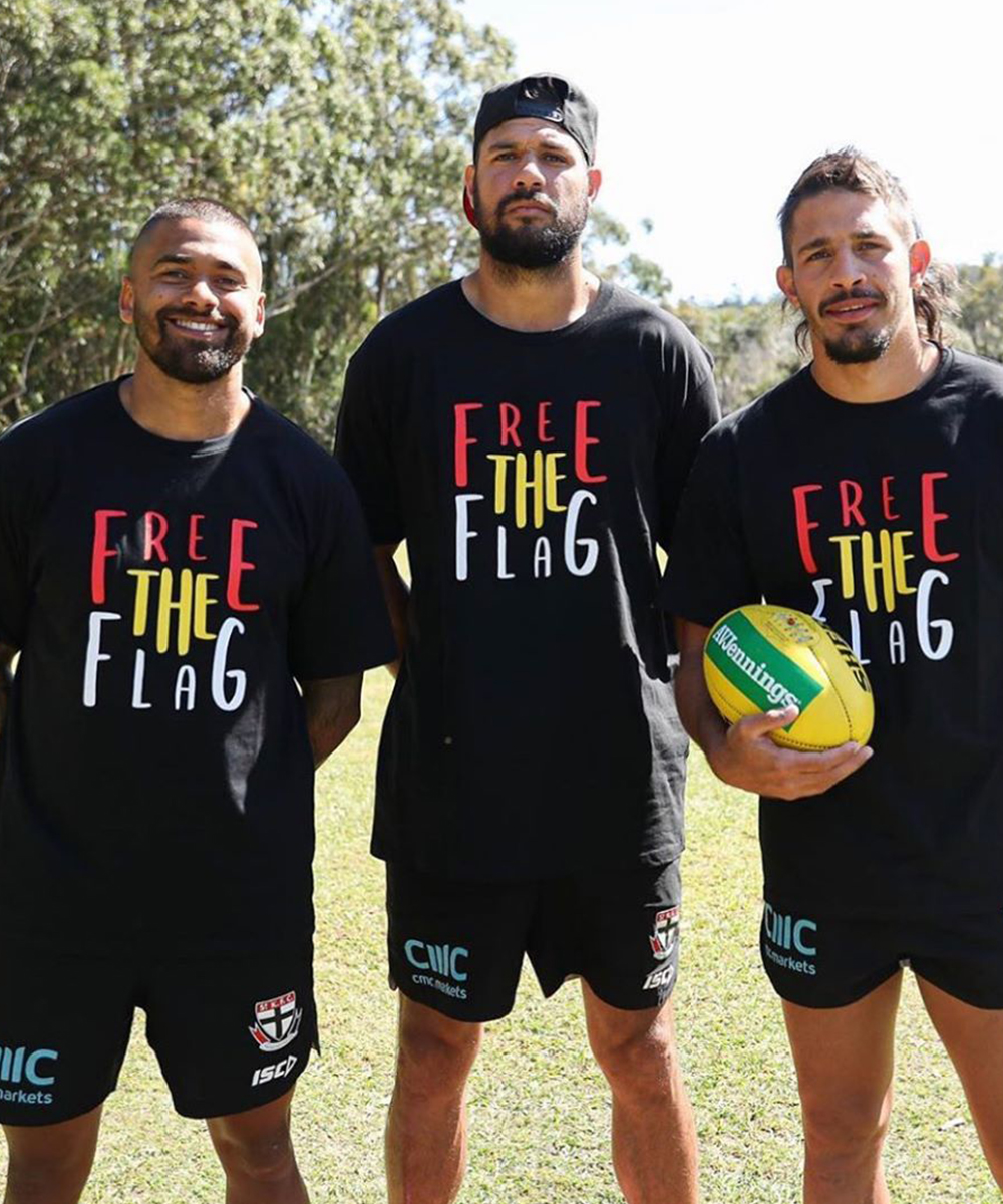 Three footballers wear Free The Flag tees