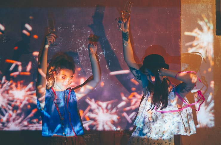 Two young women dance at a house party with a glass of wine in their hand. They're covered by a reflection of fireworks.