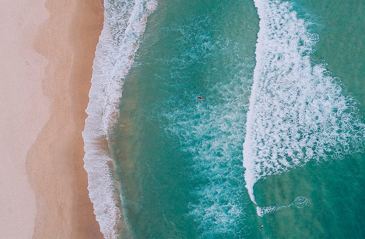 a birds eye view of a sydney beach, with waves crashing onto the sand.
