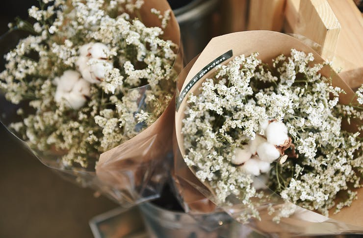 Two bunches of white flowers, wrapped in butcher's paper.
