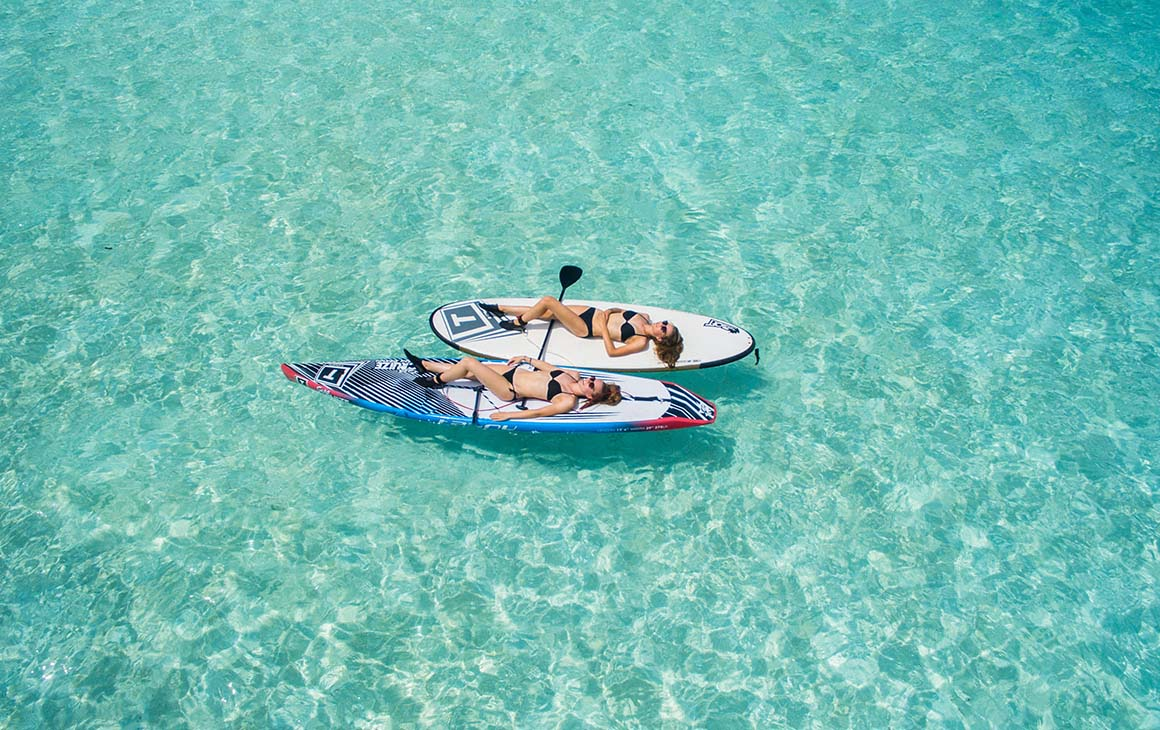 two woman lay on kayaks in crystal clear water