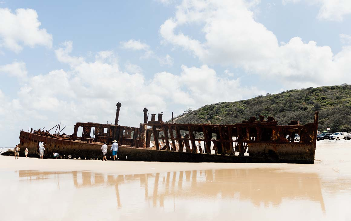 a rusty shipwreck on golden sand.