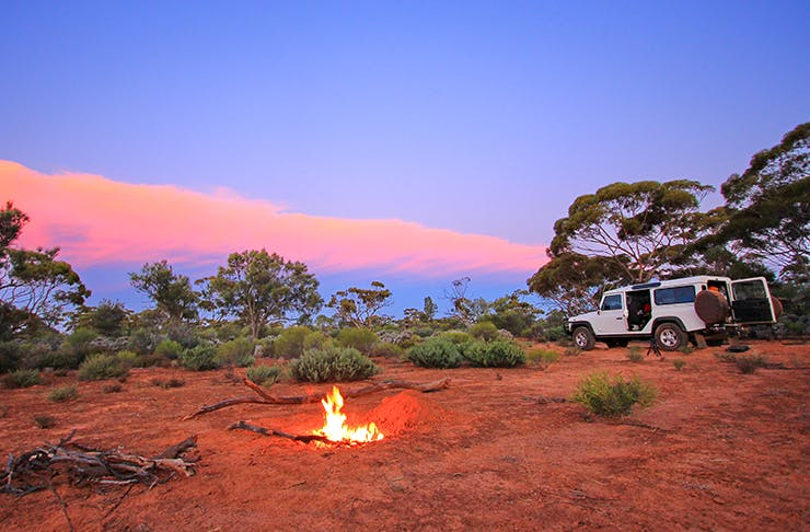 camp site set up in australian outback with small campfire at sunset