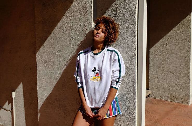 a woman in a Mickey Mouse jumper leans against a concrete wall, basking in the sun.
