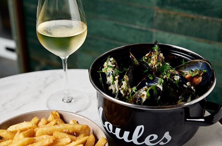 bowl of mussels, glass of wine and bowl of fries on table