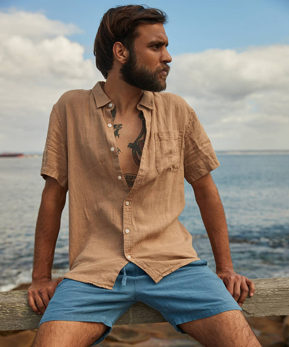 a man in a rust coloured shirt and denim shorts sits on a railing by the beach.