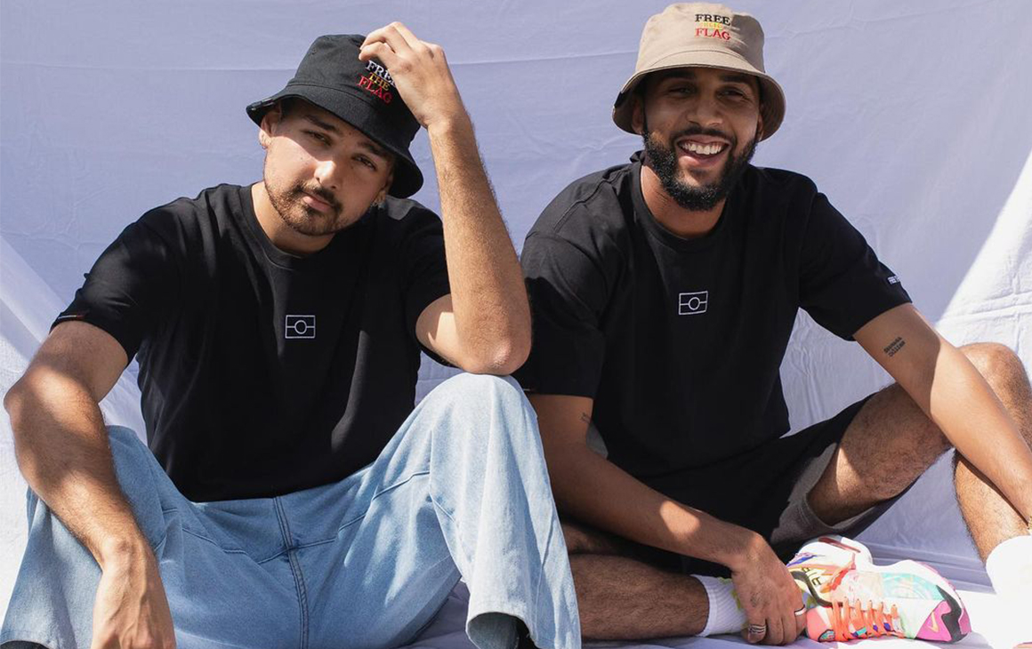 two young men sitting down wear bucket hats and black tees/