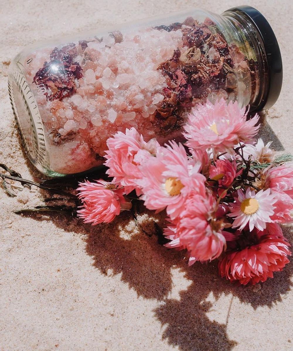 a glass jar of pink bath salts