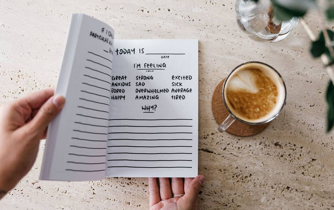 a black and white notebook next to a cup of coffee