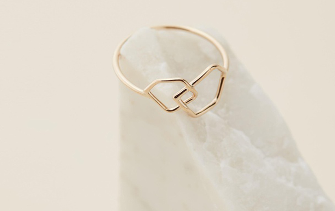 a delicate gold ring sits on a white rock.