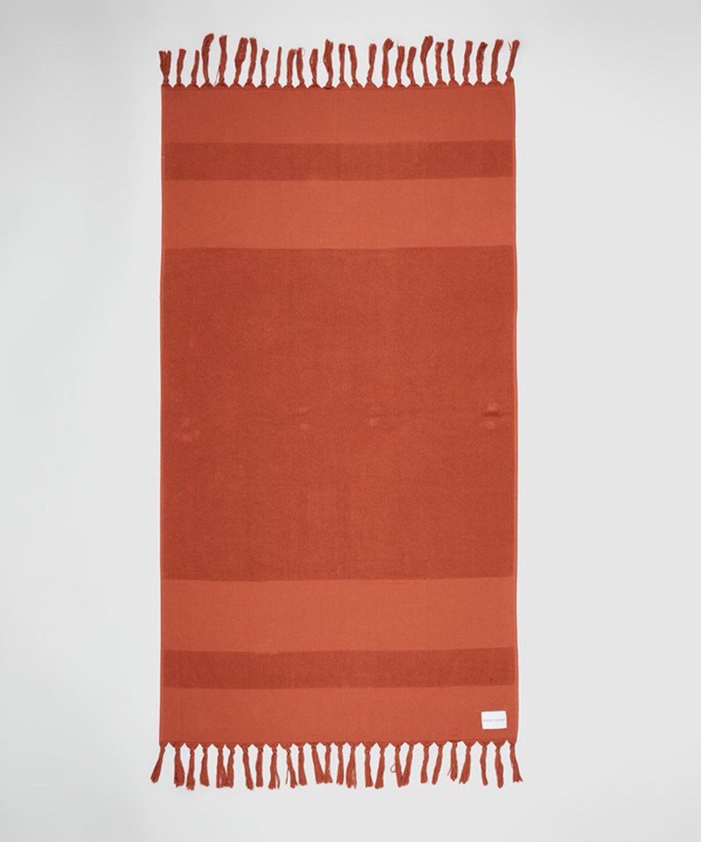 a rust coloured towel with tassels.