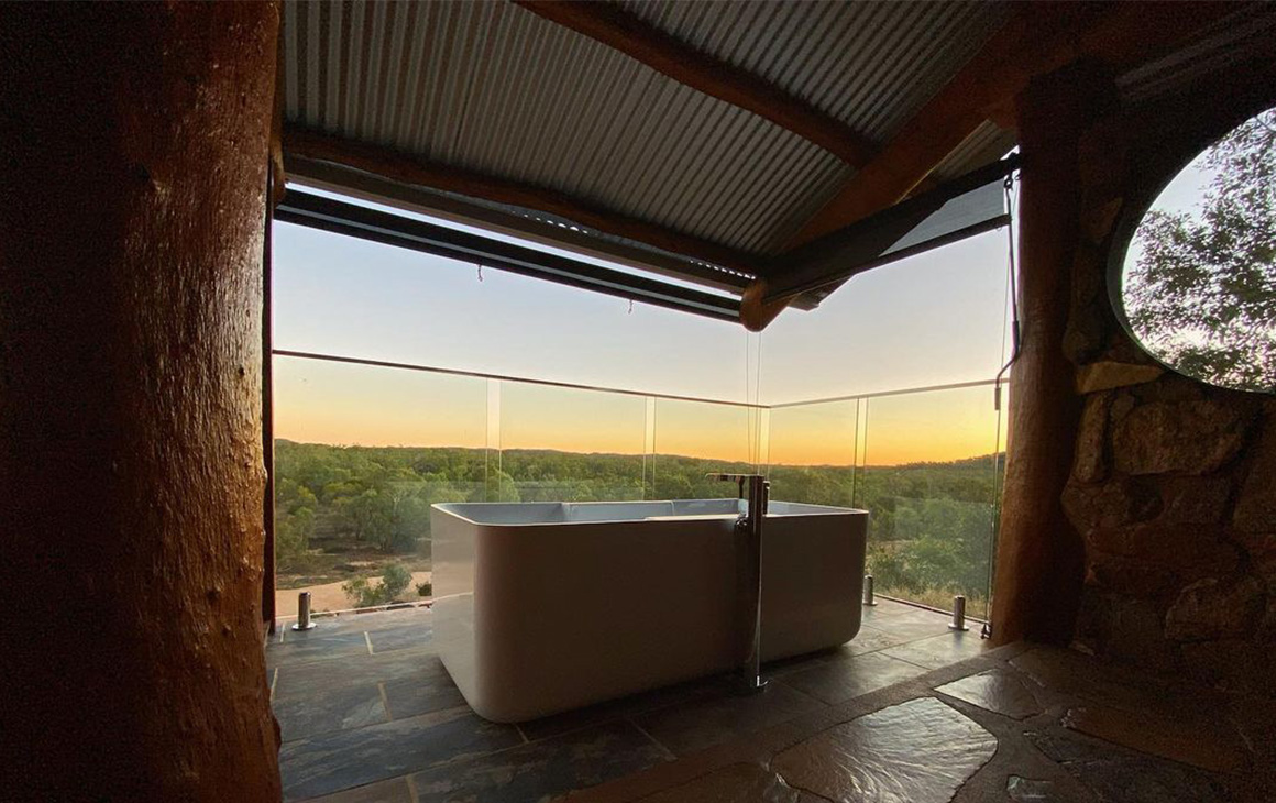a white, freestanding bath sits on a balcony at sunset.