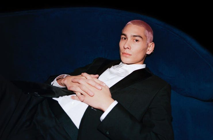 a man with pink hair, wearing a suit, reclines on a blue chair.