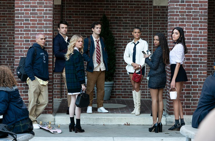 The cast of the Gossip Girl reboot stand on the steps of a brownstone building in New York