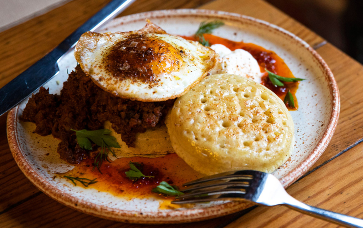 a dish at My Grandma Ben featuring a fried egg and crumpet.
