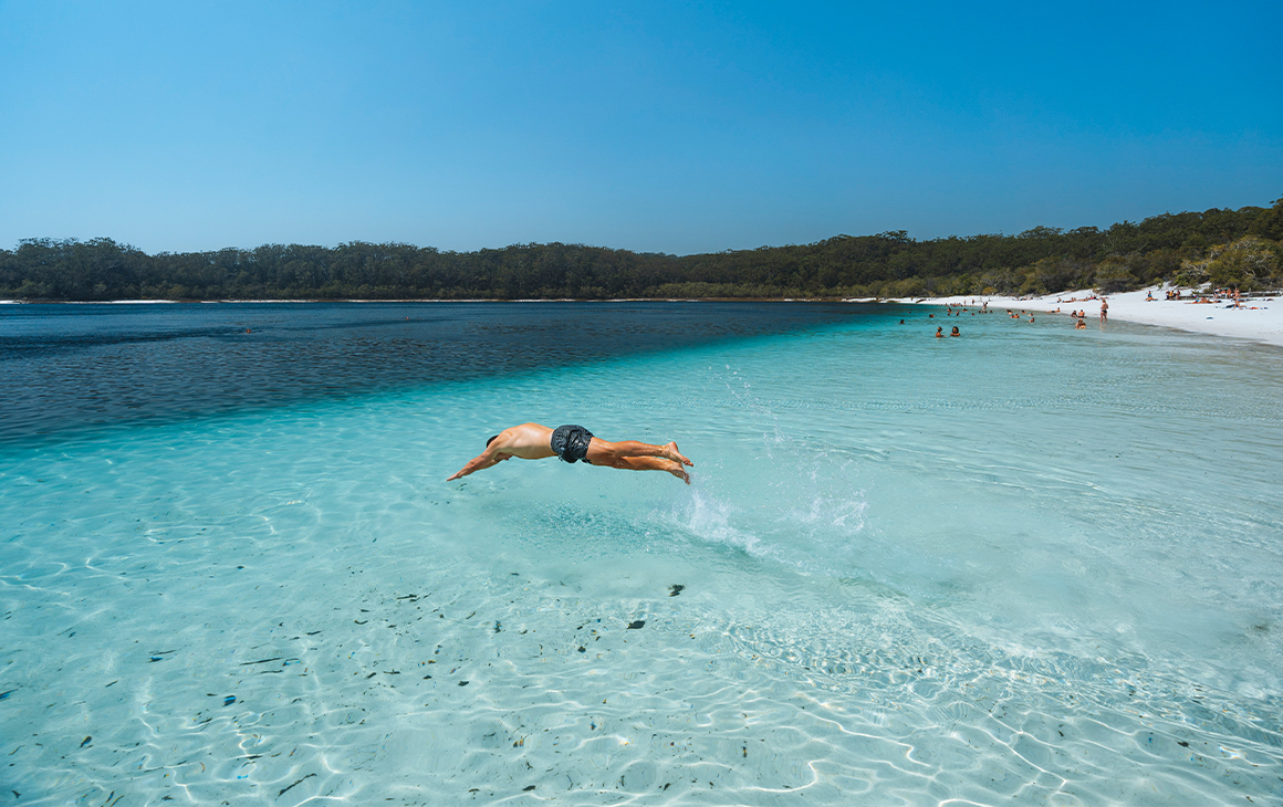 Man diving into crystal clear waters at the beach
