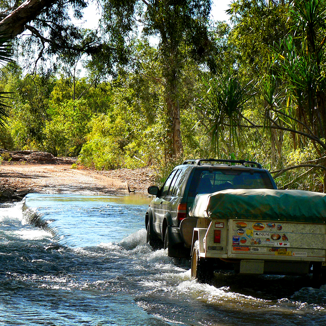 Four-wheel drive vehicle crossing a low causeway on the Gregory River during the dry season, Near Boodjamulla National Park, Gulf Country, Queensland, Australia.