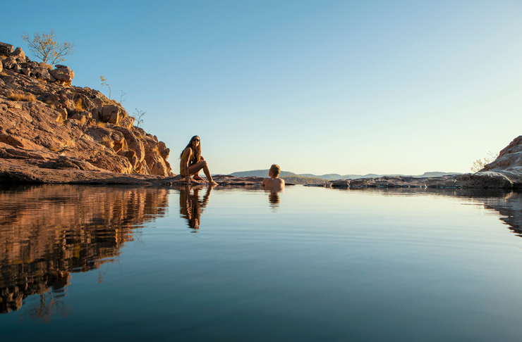 two people sitting in natural pool