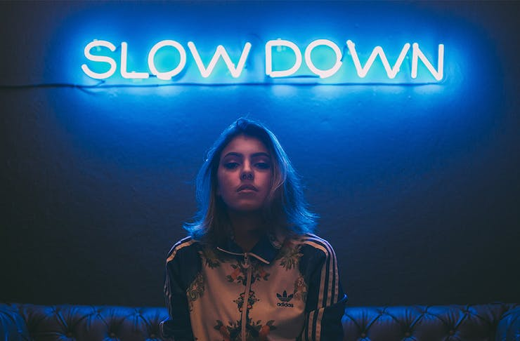 a young woman sits on a couch in front of a neon blue sign that says 'Slow Down'