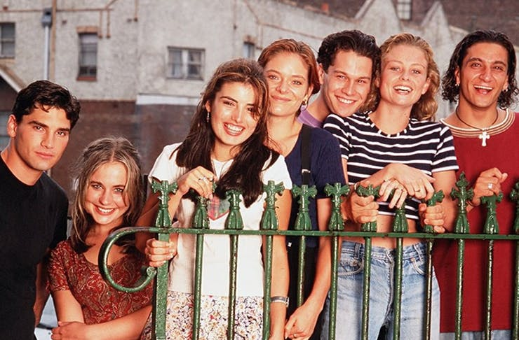 a group of male and female teens lean against a fence.